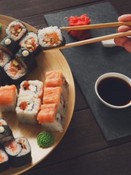 Japanese food restaurant, sushi maki roll plate, platter set. Hand take roll. Set for two with chopsticks, ginger, soy, wasabi. Sushi at rustic wood background and black stone. POV at black. Vertical.
